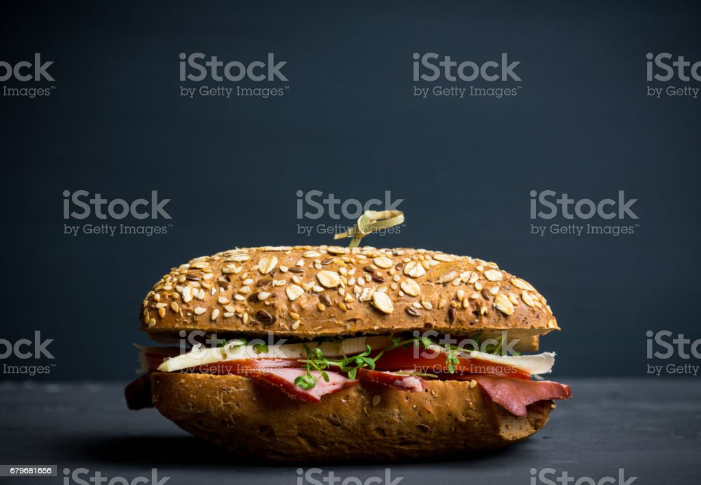 Sandwich with cereal bread, ham, tomatoes and cress on the dark background stock photo