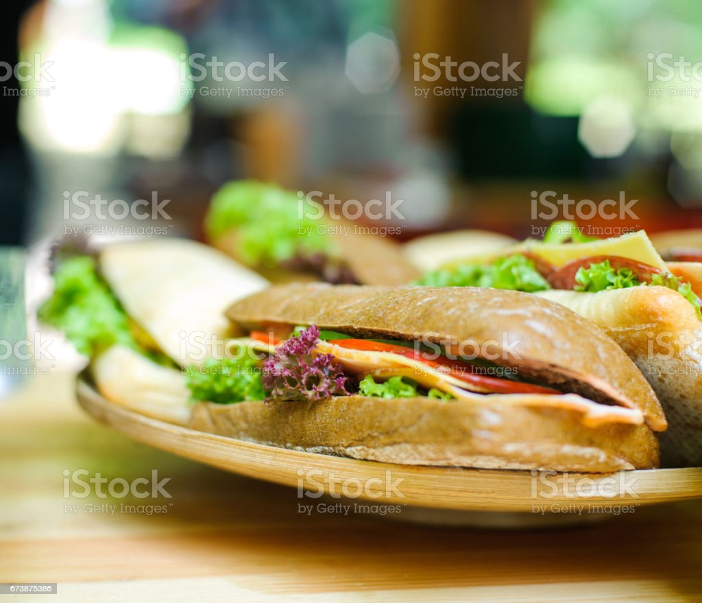 Sandwich with cheese and vegetables on a wooden board stock photo