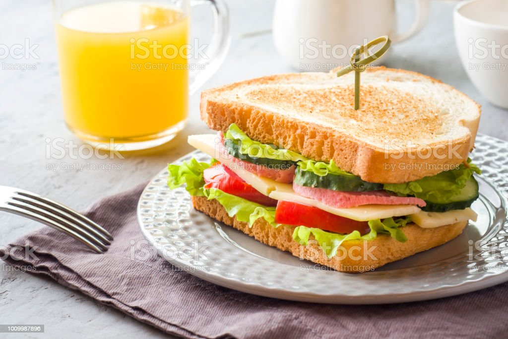 Sandwich with cheese, ham and fresh vegetables on a plate. Fresh juice and a Cup of coffee. The concept of Breakfast. stock photo