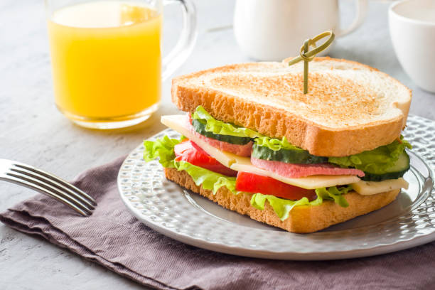 sandwich with cheese, ham and fresh vegetables on a plate. fresh juice and a cup of coffee. the concept of breakfast. - onion juice stock photos and pictures