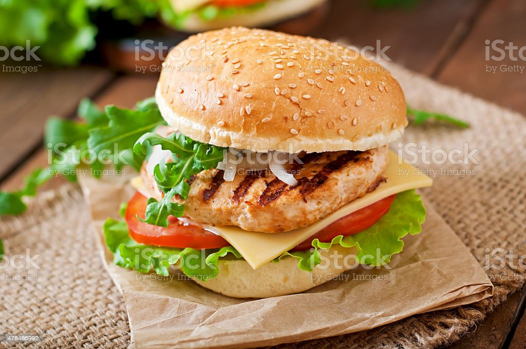 Sandwich with chicken burger, tomatoes, cheese and lettuce stock photo