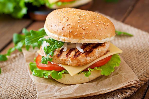 sandwich with chicken burger, tomatoes, cheese and lettuce - sandwich stockfoto's en -beelden