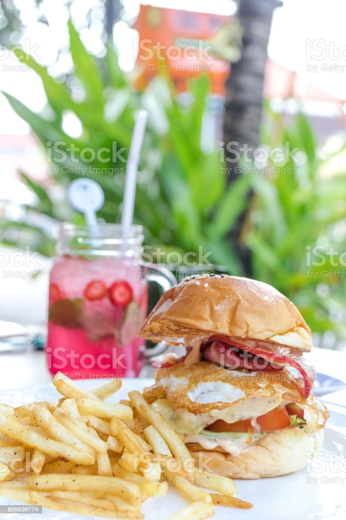 Sandwich with chicken burger, tomatoes, cheese, lettuce and french fries. Strawberry lemonade on a backgorund. Outside cafe, Bali stock photo