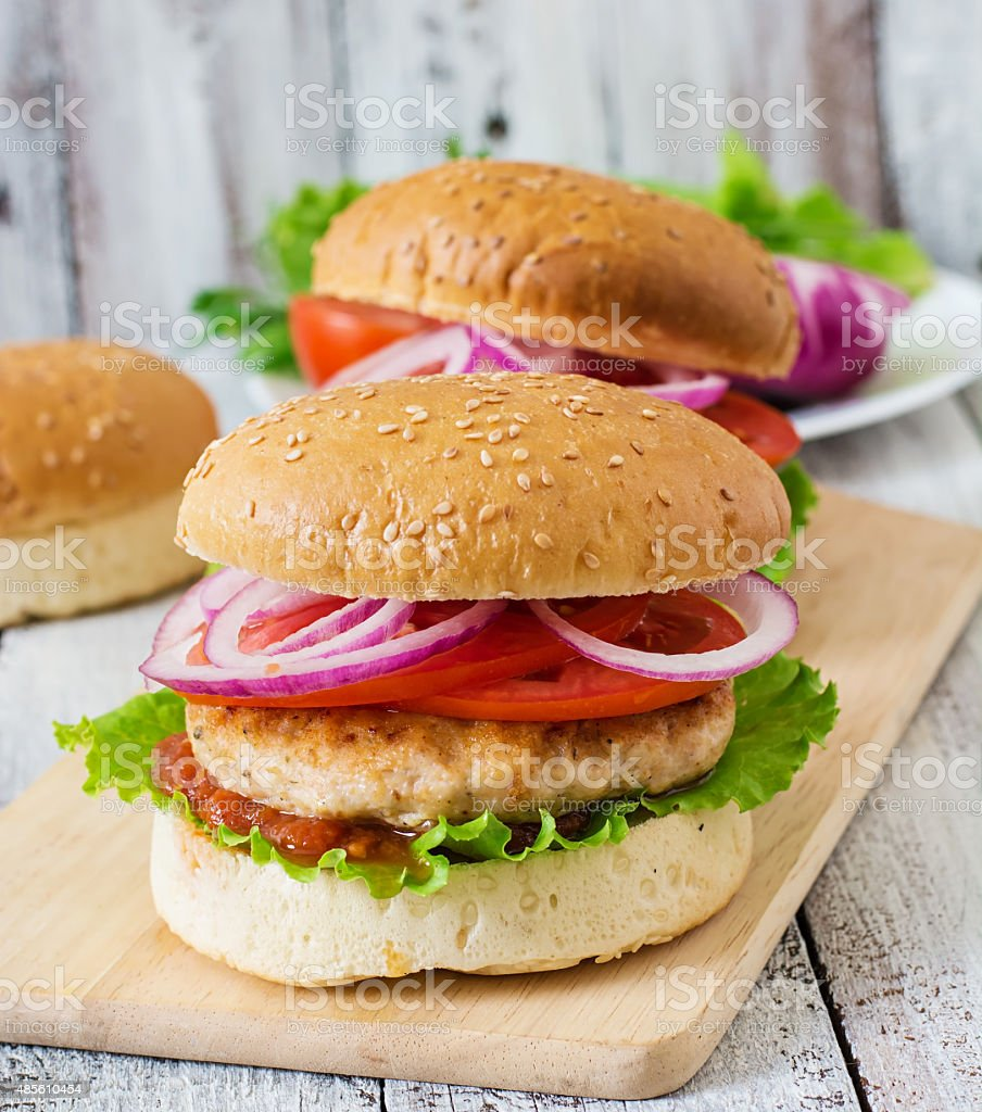 Sandwich with chicken burger, tomatoes, red onion and lettuce stock photo