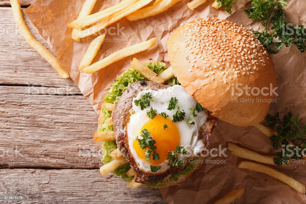sandwich with grilled meat, a fried egg and fries. horizontal stock photo