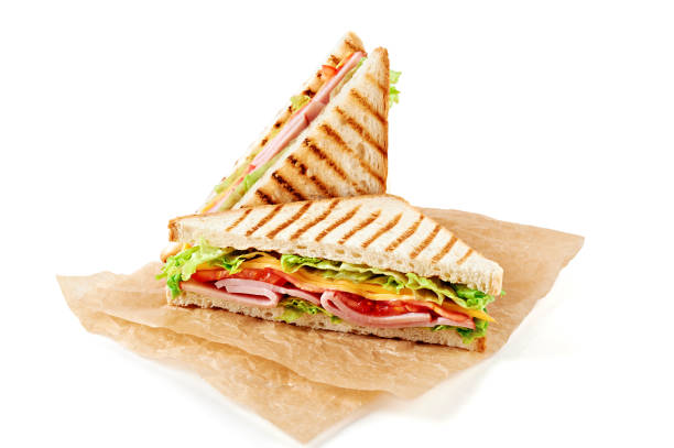 Sandwich with ham, cheese, tomatoes, lettuce, and toasted bread. Above view isolated on white background. stock photo