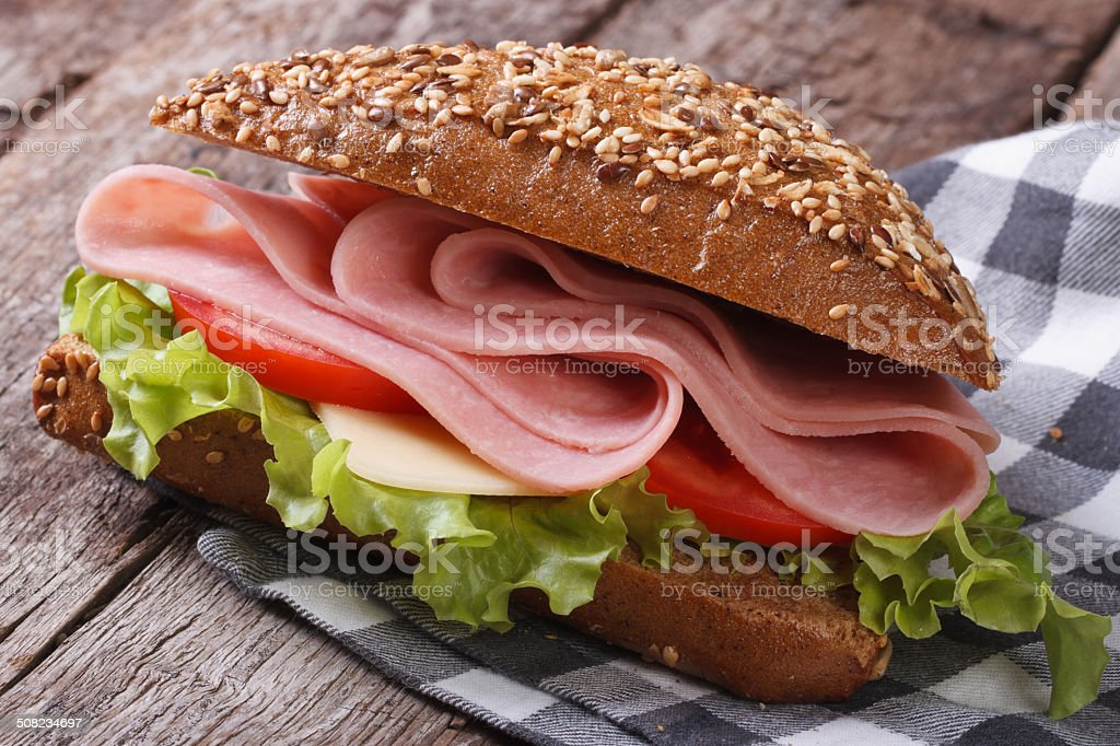 Sandwich with ham, lettuce and tomatoes on an old table stock photo