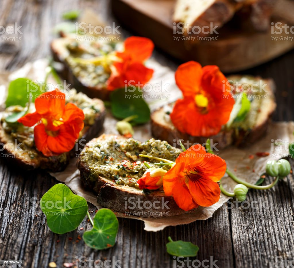 Sandwich with herb pesto and edible nasturtium flowers stock photo