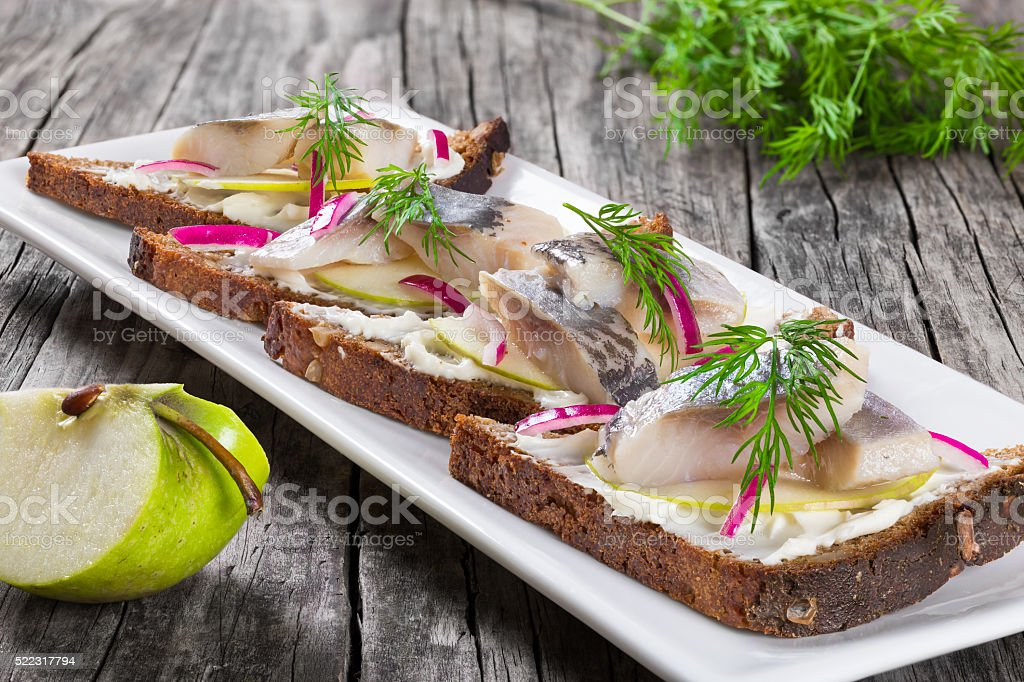 sandwich with herring fillets, onion, pickled cucumber and dill stock photo