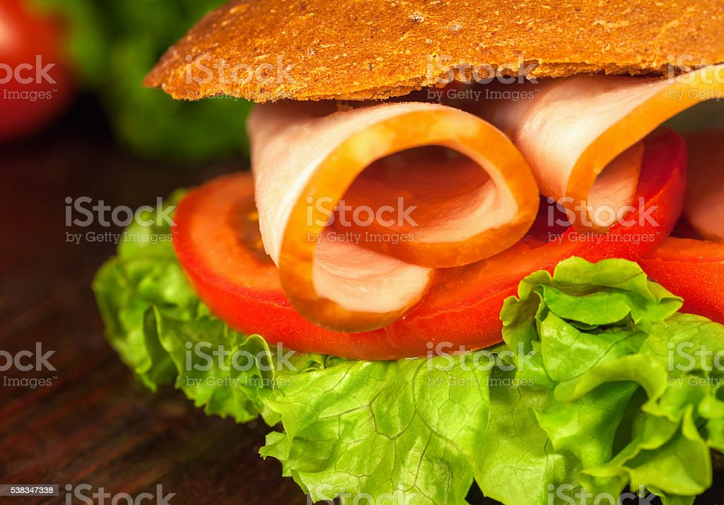 Sandwich with lettuce, tomatoes, ham, on wooden table. Closeup stock photo