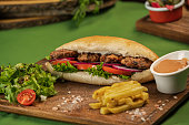 Sandwich with meatball and salad and french fries on cutting board