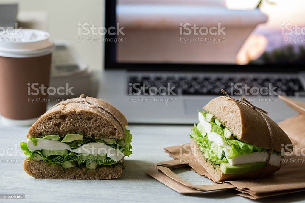 Sandwich with mozzarella, avocado, cucumber, salad and pesto stock photo