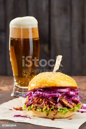istock Sandwich with pulled pork and glass of beer on wooden background 679660944