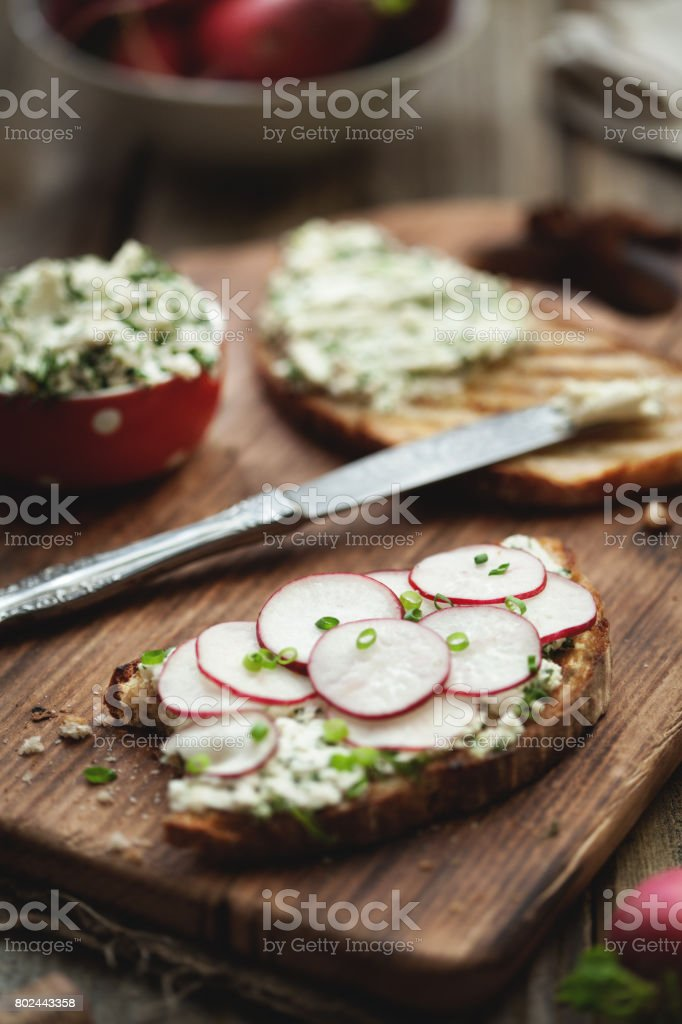 Sandwich with radish and feta cheese on a wooden table. stock photo