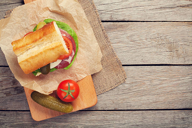 Sandwich with salad, ham, cheese and tomatoes Sandwich with salad, ham, cheese and tomatoes on cutting board. Top view with copy space submarine sandwich stock pictures, royalty-free photos & images