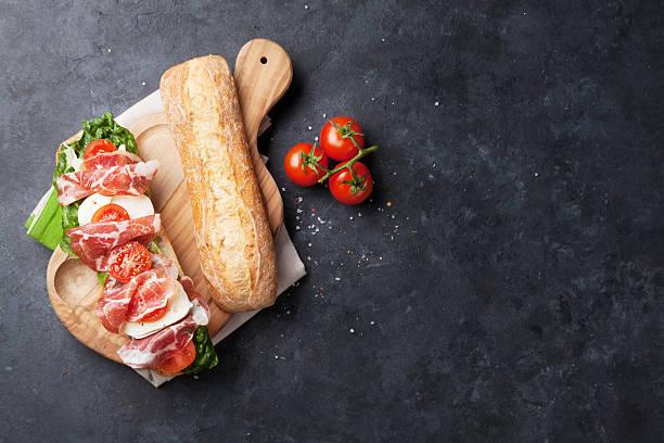 sandwich mit salat, schinken und mozzarella - brotschneidebrett stock-fotos und bilder
