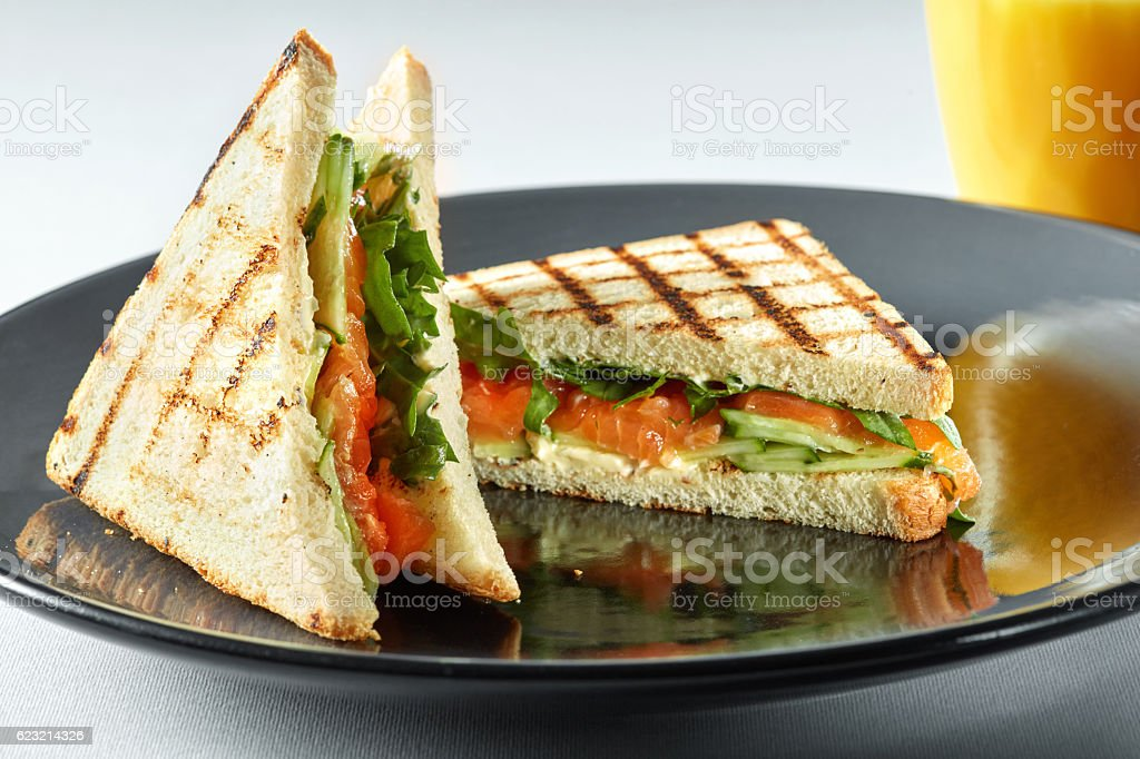 sandwich with salmon and orange juice for breakfast stock photo