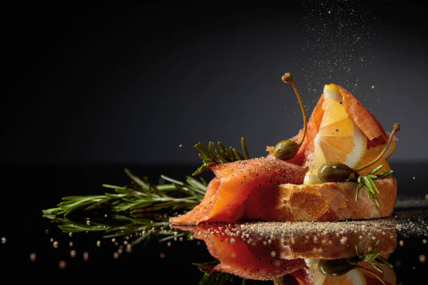 Sandwich with salmon fillet, lemon slice, capers and rosemary sprinkled with pepper. stock photo