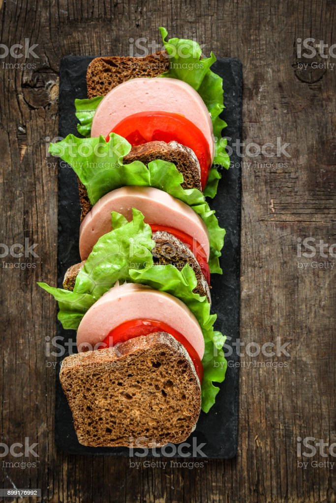 sandwich with sausage, bread, tomato and lettuce stock photo
