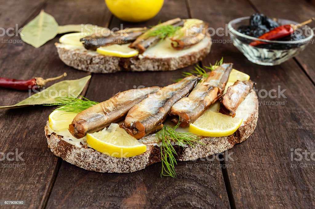 Sandwich with smoked fish capelin (sprats) stock photo