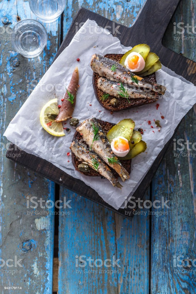 Sandwich with sprats and egg on wooden table, close up stock photo
