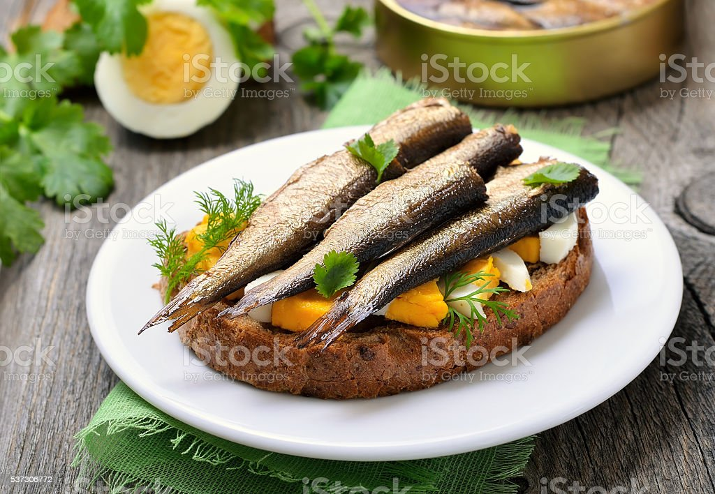 Sandwich with sprats and egg on wooden table stock photo