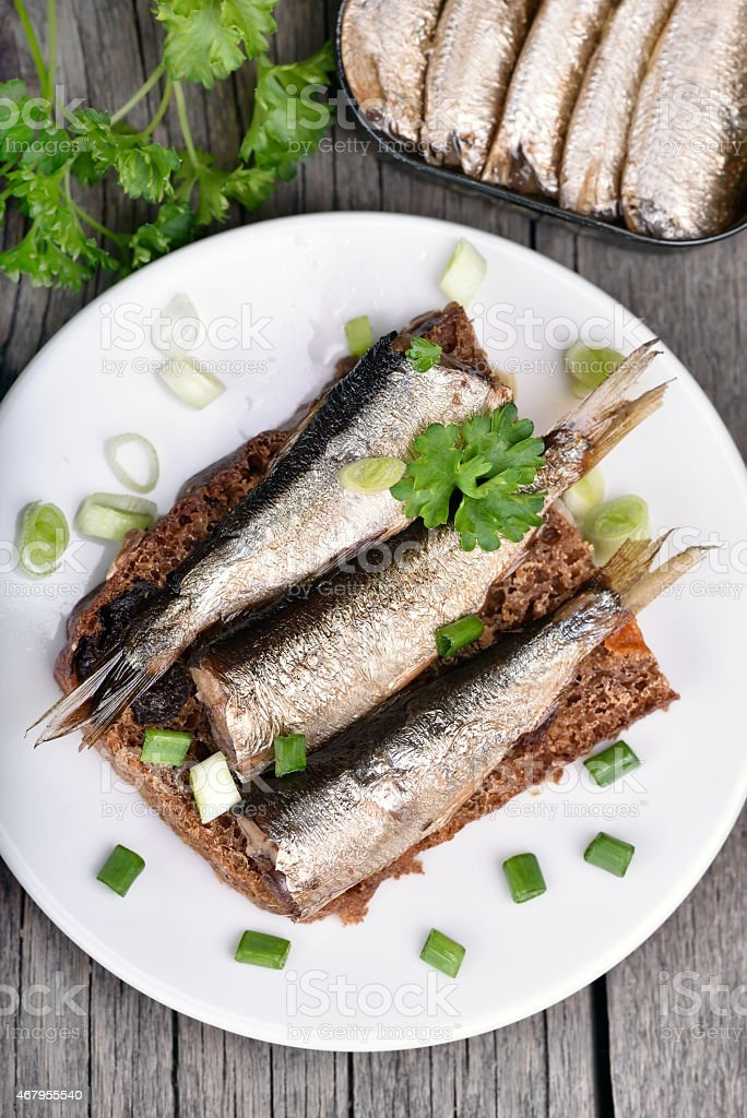 Sandwich with sprats on wooden table stock photo