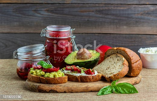 istock Sandwich with sun-dried tomatoes, avocado, basil, curd cheese on croutons. Vegetarian breakfast or snack 1273222730