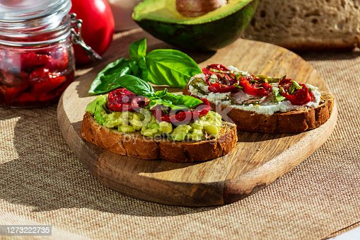 istock Sandwich with sun-dried tomatoes, avocado, basil, curd cheese on croutons. Vegetarian breakfast or snack 1273222735