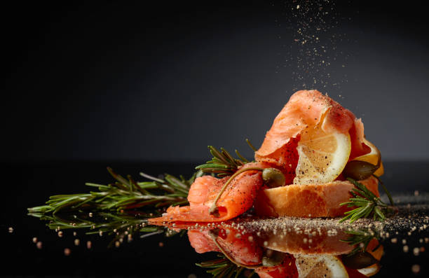 Sandwich with trout fillet, lemon slice, capers and rosemary sprinkle with pepper. Sandwich with trout fillet, lemon slice, capers and rosemary sprinkle with pepper. Black reflective background. Copy space. gourmet stock pictures, royalty-free photos & images