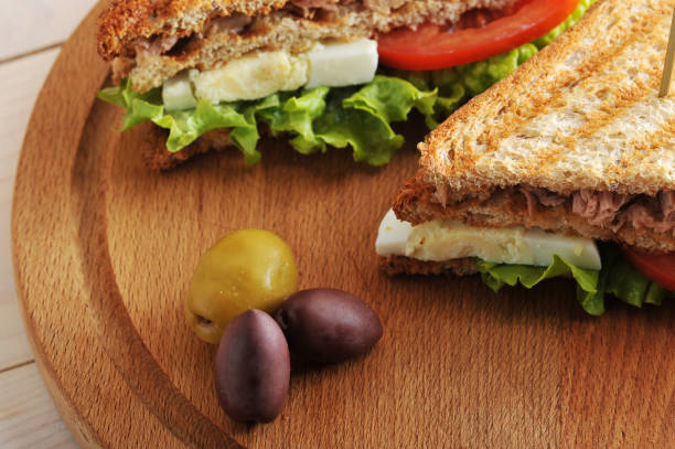 Sandwich with tuna from white toasted bread. Filling of tuna, eggs, tomato, green salad.american,background,big,bread,breakfast,breast,closeup,club,cuisine,egg,food,fresh,green,grill,grilled,healthy,herb,lunch,macro,meal,plate,red,roasted,salad,sandwich,s stock photo