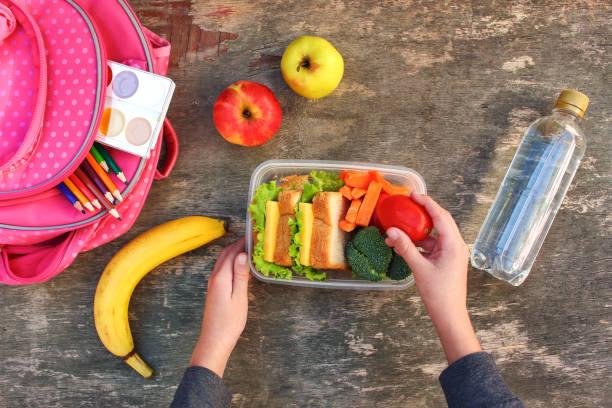 sanduíches, frutas e legumes na caixa do alimento, mochila em fundo de madeira velho. conceito de criança comer na escola. vista superior. plano de leigos. - almoço - fotografias e filmes do acervo