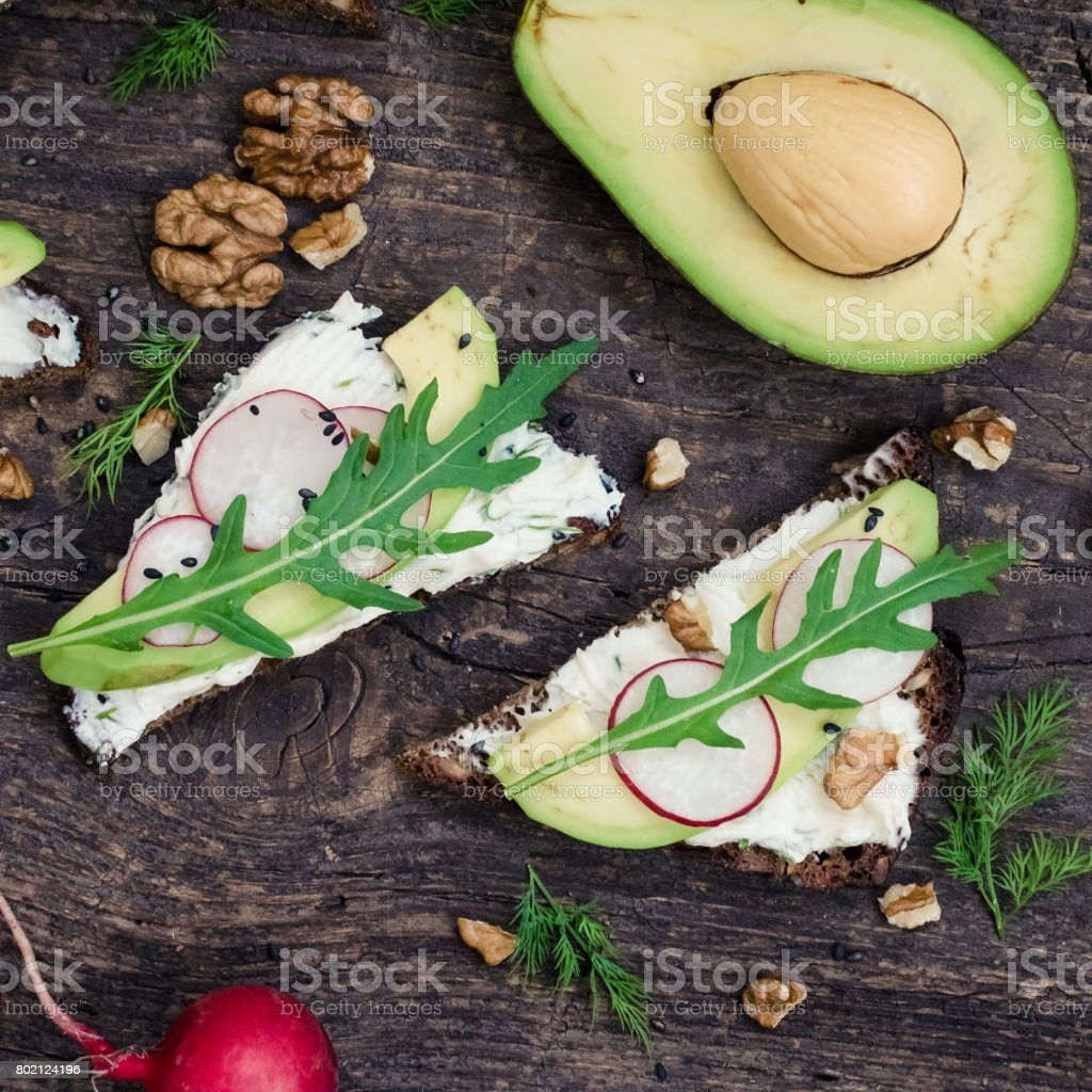Sandwiches of rye bread with avocado and goat cheese stock photo