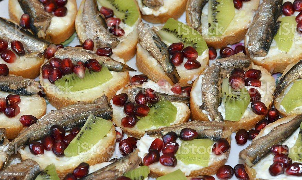 Sandwiches sprat, kiwi and pomegranate seeds stock photo