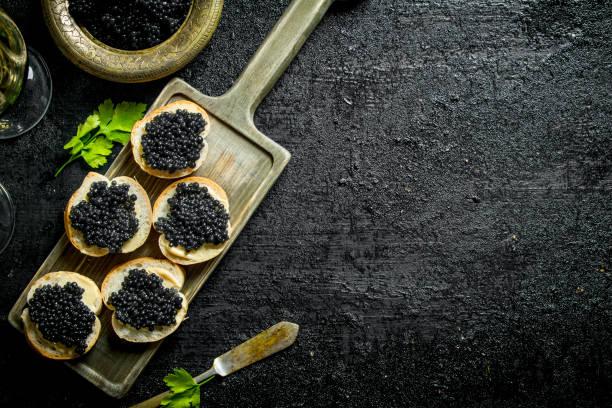 bocadillos con caviar negro en la tabla de cortar. - caviar fotografías e imágenes de stock