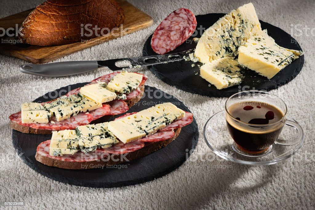 Sandwiches with cheese of Dorblu and raw smoked sausage on black slate plates, a cheese knife and a cup of hot coffee стоковое фото