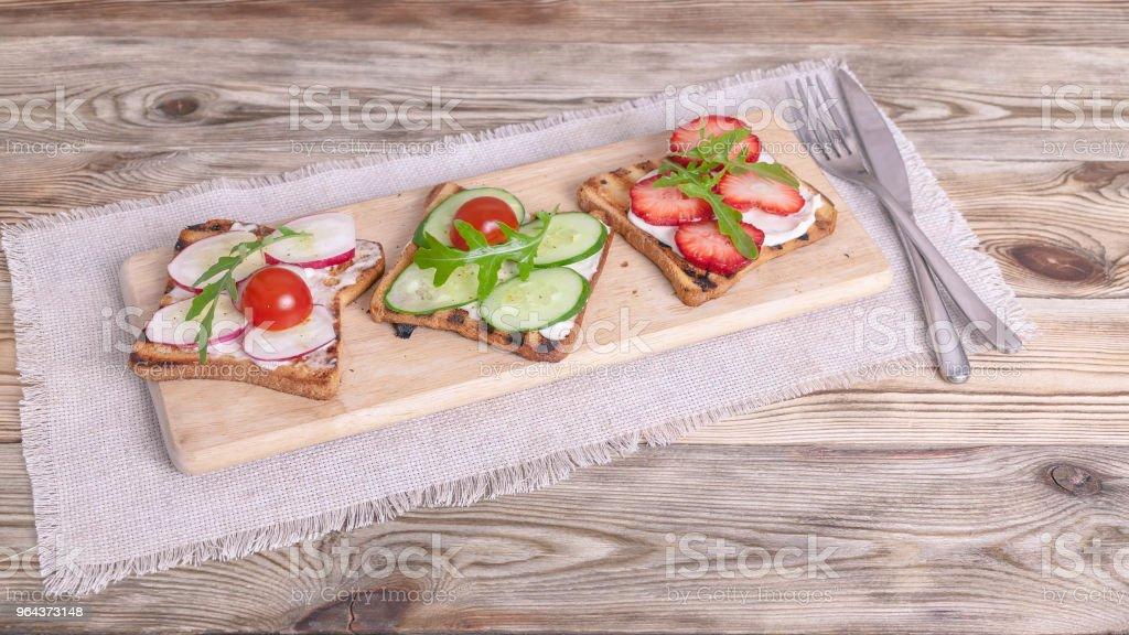 Sandwiches met roomkaas, radijs, verse komkommer, aardbeien en rucola. Banner - Royalty-free Aardbei Stockfoto