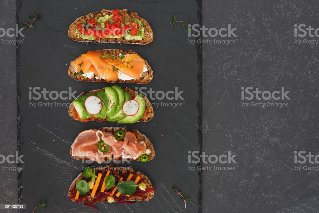 Sandwiches with dark rye bread and different toppings stock photo