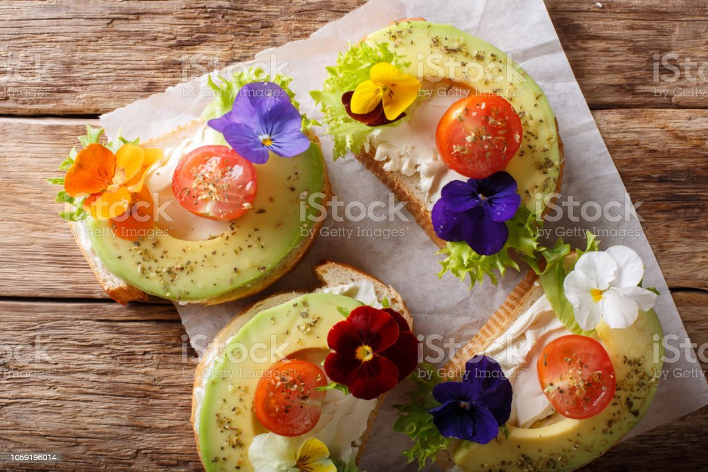 Sandwiches with edible flowers, fresh avocado and cream cheese close-up. horizontal top view stock photo