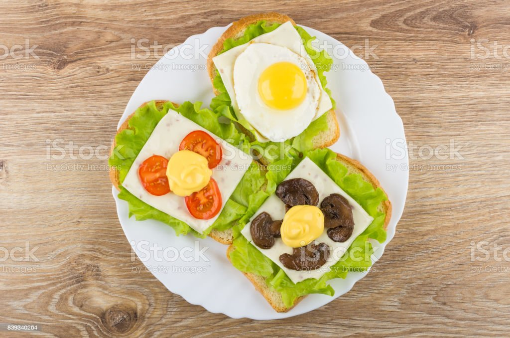 Sandwiches with lettuce, cheese, mushrooms, tomato and fried egg stock photo