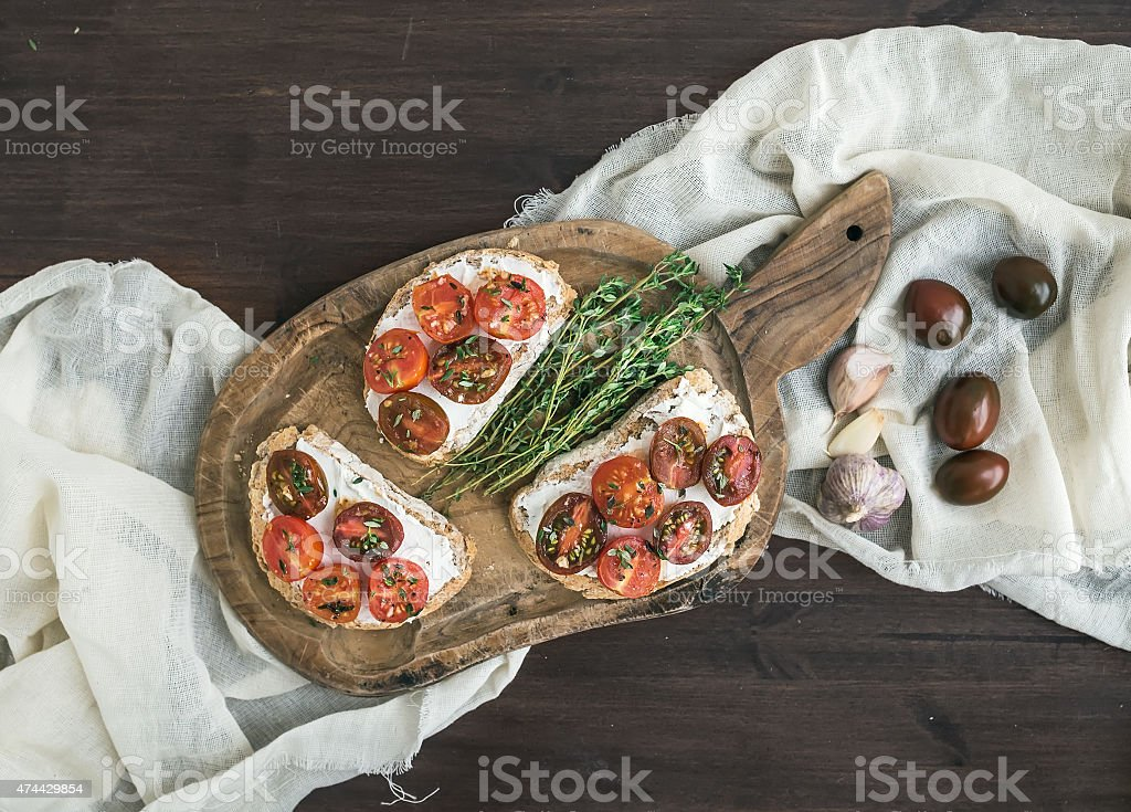 Sandwiches (bruschetta) with roasted cherry tomatoes, soft cheese stock photo