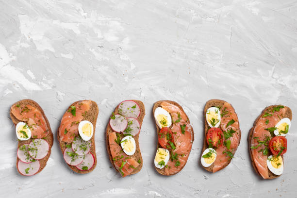 sandwiches with salmon, cured bresaola, cherry tomatoes, boiled quail eggs and sour cream. japanese meal - bresaola foto e immagini stock