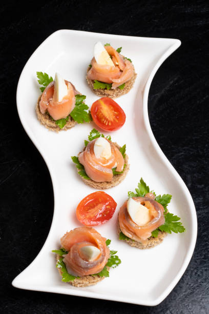 sandwiches with salmon, cured bresaola, crayfish, tomatoes, quail eggs and sour cream. japanese meal - bresaola foto e immagini stock