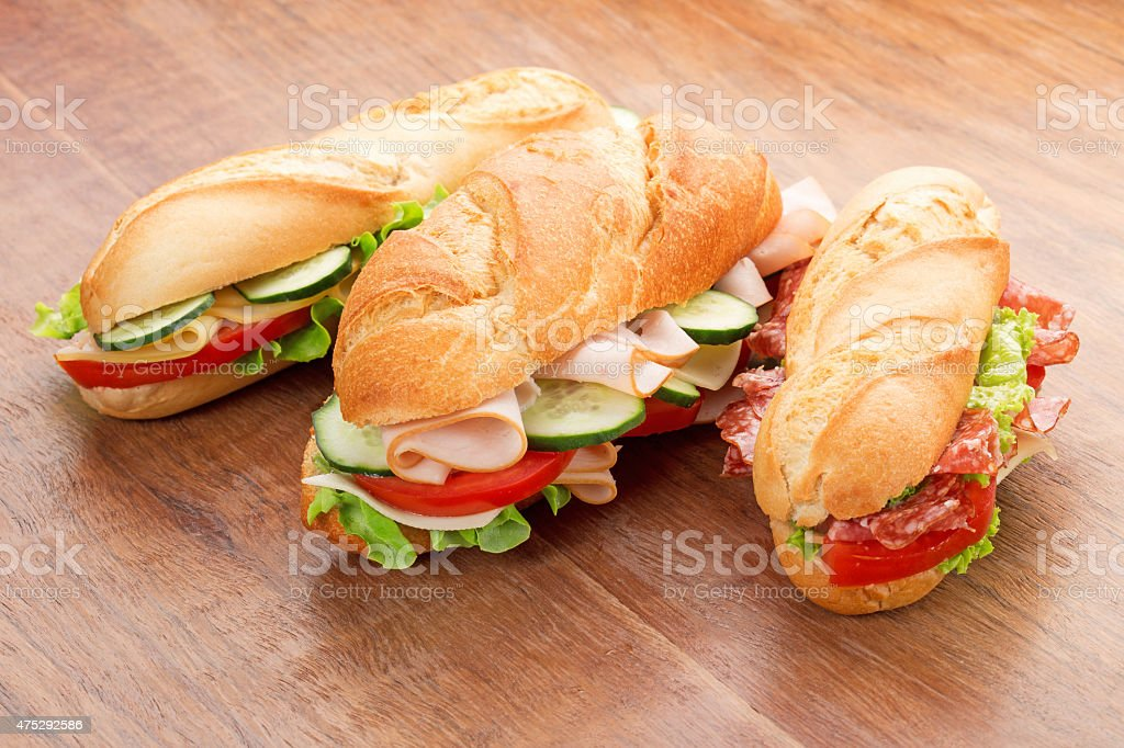 sandwiches with savory fillings on wooden table stock photo