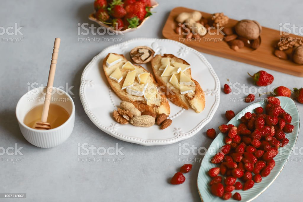 sandwiches with strawberries, cheese, camembert, brie, nuts and honey on the bruschetta Top view stock photo