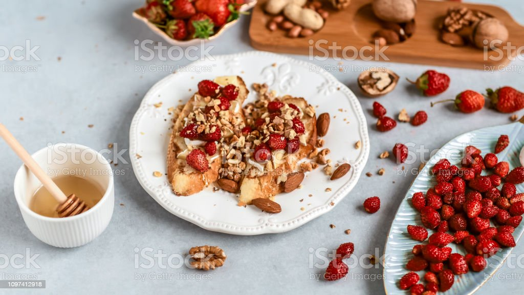 sandwiches with strawberries, cheese, camembert, brie, nuts and honey on the bruschetta Top view. Food recipe stock photo