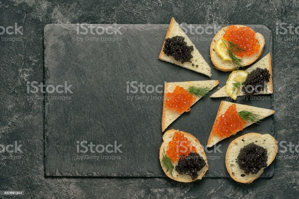 sandwiges with red salmon and black stugeon caviar on a black stone board on a black table, top view with copy space. stock photo