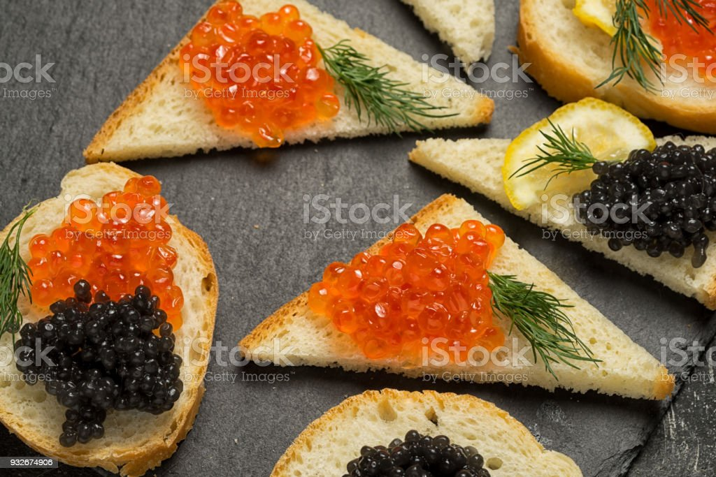 sandwiges with red salmon and black stugeon caviar on a black background, top view. stock photo