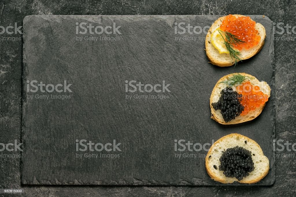 sandwiges with red salmon caviar and black stugeon caviar on a black stone board on a black table, top view with copy space at the side. suitable for restaurant menu template. stock photo