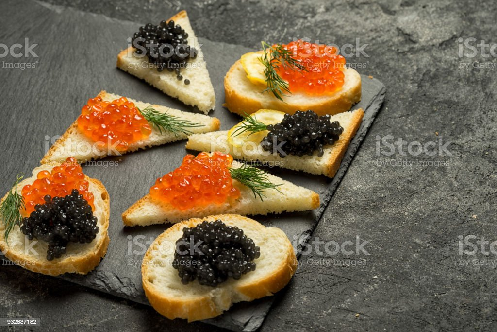 sandwiges with red salmon caviar and black stugeon caviar on a black stone board on a black table, side view with copy space. stock photo